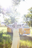 Young woman with arms outstretched in field by camper van, smiling (lens flare). Young women with arms outstretched in field by camper van, smiling (lens flare Royalty Free Stock Image