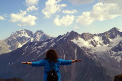 Young woman with arms outstretched in the mountains. The concept of happiness, freedom, pleasure. stock photography