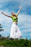 Young woman with arms raised against nature Stock Image