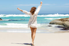 Young woman with arms raised in the air at the beach Stock Photography