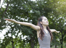 Young woman arms raised enjoying the fresh air Stock Photo