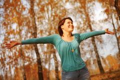 Young woman arms raised enjoying the fresh air in autumn forest Royalty Free Stock Photos