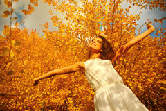 Young woman arms raised enjoying the fresh air in autumn forest Stock Photos