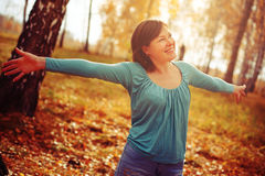 Young woman arms raised enjoying the fresh air in autumn forest Stock Photography