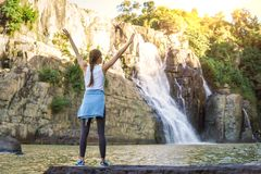Young woman with arms wide open standing on rock near waterfall Royalty Free Stock Images