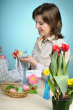 Young woman arranging easter eggs Stock Image