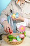 Young woman arranging easter eggs Stock Images