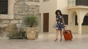 Young woman arrives in beautiful exotic city on vacation, heading for hotel. Stock footage stock footage
