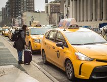 Traveler Gets Taxi - Penn Station - New York, NY. Young woman arrives with luggage at taxi line outside Penn Station in New York City Stock Photos