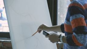 Young woman artist in apron painting picture on canvas in art studio. A slender girl draws a pencil on canvas by the window stock video footage