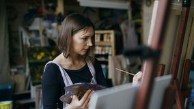 Young woman artist in apron painting picture on canvas in art studio. Indoors stock video footage