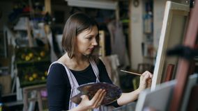 Young woman artist in apron painting picture on canvas in art studio royalty free stock image