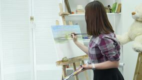 Young woman artist in apron painting picture on canvas in art studio.  stock footage