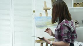 Young woman artist in apron painting picture on canvas in art studio.  stock video footage