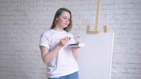 Young woman artist in apron painting picture on canvas in art studio.  stock video