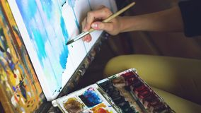 Young woman artist draw pictrure with watercolor paints and brush on easel canvas closeup hand. In studio indoors Stock Photography