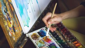 Young woman artist draw pictrure with watercolor paints and brush on easel canvas closeup hand. In studio indoors Royalty Free Stock Photo