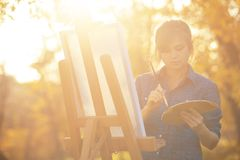 Young woman artist drawing a picture on canvas on an easel in nature, a girl with a brush and a palette of paints working inspired royalty free stock photos