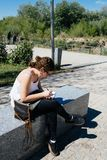 Young woman artist drawing sketches in a park. Young woman artist drawing sketches sitting on a bench in a park in Cordoba near Roman Bridge Stock Image