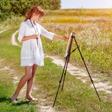 Young woman artist at the easel painting landscape outdoors. Girl-artist working on the plein air. Young woman artist at the easel painting landscape. Girl royalty free stock images