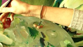Young woman artist painting an artwork picture using oil painting palette. 4K close-up video stock video footage