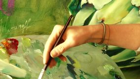 Young woman artist painting an artwork picture using oil painting palette. 4K close-up video stock video