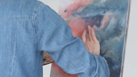 Young woman artist painting at home creative painting back view stock video footage
