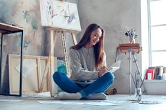 Young woman artist painting at home creative planning Stock Image