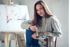 Young woman artist painting at home creative holding palette stock photos