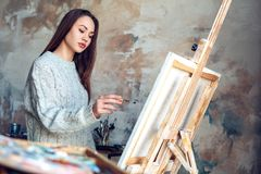 Young woman artist painting at home creative standing making abstract picture stock photography