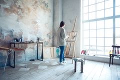 Young woman artist painting at home creative standing drawing. Young woman artist painting at home standing drawing near the window inspiration full body messed Royalty Free Stock Photos