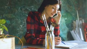 Young woman artist painting scetch on paper notebook with pencil and talking phone indoors. Young woman artist painting scetch on paper notebook with pencil and Royalty Free Stock Photography