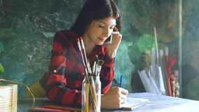 Young woman artist painting scetch on paper notebook with pencil and talking phone indoors. Young woman artist painting scetch on paper notebook with pencil and Royalty Free Stock Images
