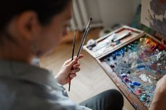 A young woman artist paints an oil painting on the easel. stock photography