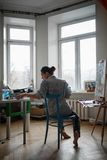 A young woman artist paints an oil painting on the easel. Vertical photo. A young woman artist sits in a bright studio on a blue chair and paints a picture in stock photos