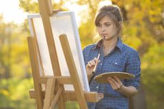 A young woman artist standing in front of an easel with a brush and thinking that a girl paints a picture in nature on a lawn. Flooded with sunlight in summer stock image