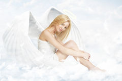 Young woman as angel sitting on clouds. Young woman as an angel sitting on clouds with white wings and aureole stock photos