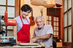 Young woman as apprentice in wood construction. Young women as apprentice in wood construction learns with luthier stock images