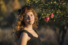 Young woman as cat on Halloween picking apples from trees Stock Photos