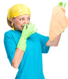 Young woman as a cleaning maid. Holding rag and pinching her nose because of bad smell, isolated over white stock photography
