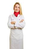 Young woman as cook in apprenticeship. Young smiling woman as cook in apprenticeship with workwear stock photo