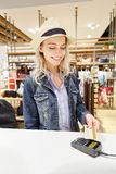 Young woman paying with credit card at checkout. Young woman as a customer pays by credit card at the mall at checkout Stock Photography