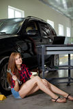 Young woman as a mechanic in checked shirt witch wrench in garage Stock Photography