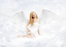 Young woman as na angel. Young blond woman as na angel with white wings sitting on clouds stock photography