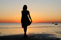 Young woman as silhouette by the sea Royalty Free Stock Photos