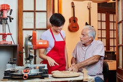 Young woman as trainee learns with luthier. Young women as trainee learns with master luthier in workshop Stock Photos