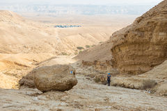 Young woman ascending desert mountain slope. Royalty Free Stock Photos