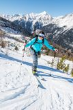 Young woman ascending a slope on skis. Royalty Free Stock Photo