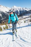 Young woman ascending a slope on skis. Stock Photos