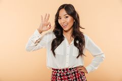 Young woman with asian appearance showing alright gesture being. Young woman with asian appearance showing alright gesture, being happy and isolated over peach stock photos